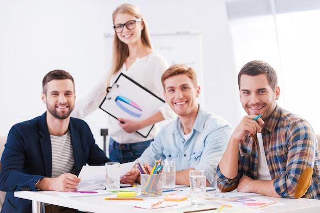 Творческий коллектив. четыре веселых деловых человека в элегантной повседневной одежде сидят вместе за столом и смотрят в камеру