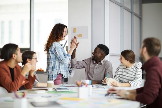 Creative team high-five in meeting