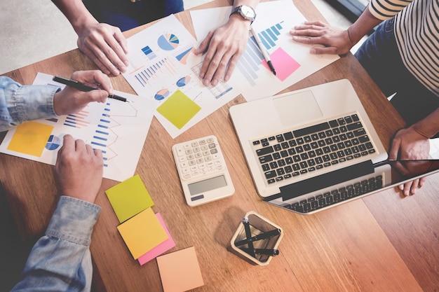 クリエイティブチームの仕事。スタートアッププロジェクトを担当する若いビジネスマンは、グラフプランを分析し、ワークスペースオフィスで議論し、ブレーンストーミングのコンセプトを考えます。
