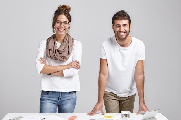 Creative team of two happy male and female colleagues in casual clothes standing at desk,