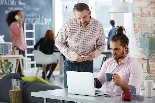 Креативная команда, использующая ноутбуки и телефоны в коворкинг-офисе