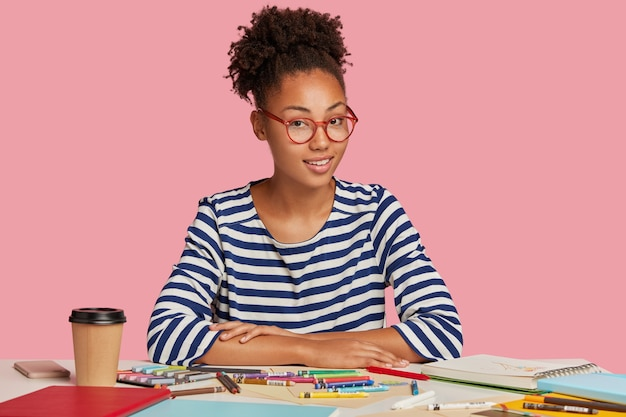 Creative teenage artist or illustrator wears casual clothes, has inspiration for drawing, surrounded with notebook and colourful markers