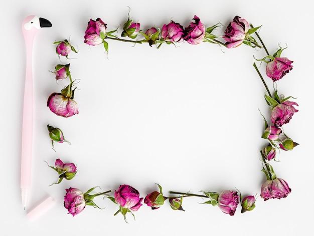 創造的なテンプレートまたはモックアップ。乾燥したピンクのバラとペンのフレーム。上面図。コピースペース。