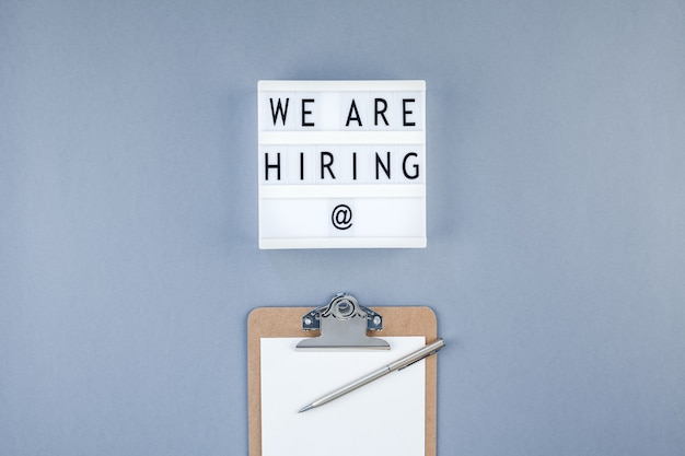 Creative top view flat lay of desk with we are hiring text on lightbox