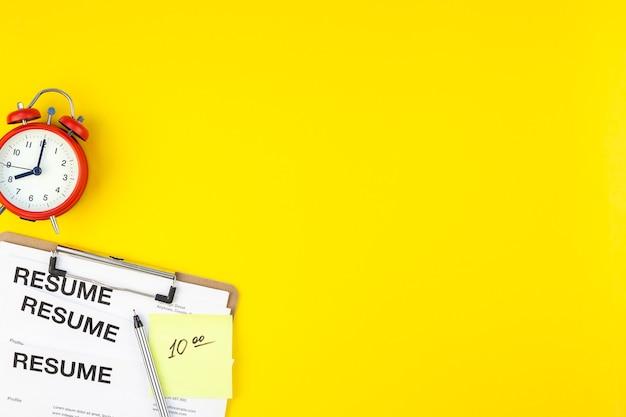 최소한의 스타일로 굵은 노란색 배경에 이력서 문서 복사 공간이있는 책상의 창조적 인 평면도 평면 누워. 새로운 직업의 개념, 채용 프로세스, 새로운 팀원 심사
