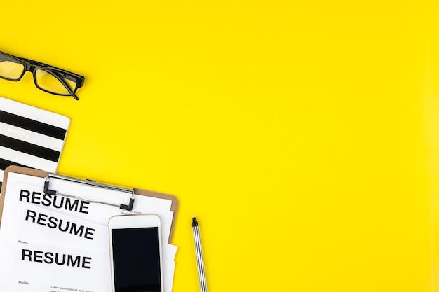 최소한의 스타일로 굵은 노란색 배경에 이력서 문서 복사 공간이있는 책상의 창조적 인 평면도 평면 누워.