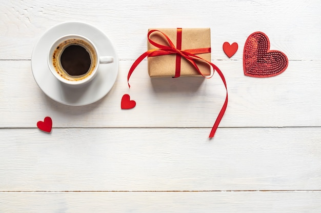 Creative top view flat lay romantic composition. hot espresso coffee mug with red gift hearts and craft present box. concept or birthday or valentines holiday with copy space.
