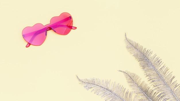 현대적인 선글라스로 창의적인 평면도. 심장 모양의 안경 파스텔 컬러. 최소한의 여름 개념