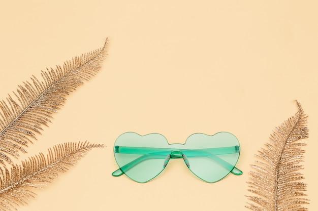현대적인 선글라스로 창의적인 평면도. 심장 모양의 안경 파스텔 컬러. 최소한의 여름 개념.