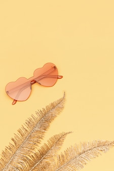 Creative top view with modern sunglasses on paper background. heart shaped eyeglasses pastel colored. minimal summer concept. flat lay with copy space.