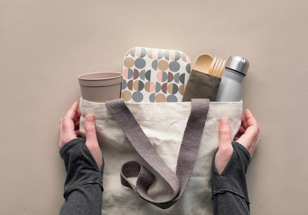 Creative top view, zero waste packed lunch kit in canvas bag. hands holding bag with takeaway lunch box, bundle with bamboo cutlery, reusable box and coffee-to-go cup. flat layout on craft paper.
