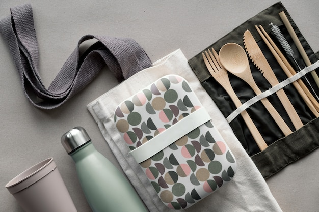 Creative top view, zero waste packed lunch kit, takeaway lunch box set on cotton bag, organizer of bamboo cutlery, reusable box and coffee-to-go cup. sustainable lifestyle, flat layout on craft paper.