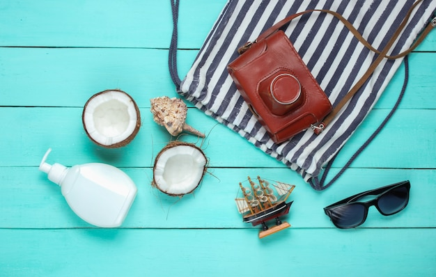 Creative travel background. beach accessories, retro camera, coconut on blue wooden background. flat lay summer style.