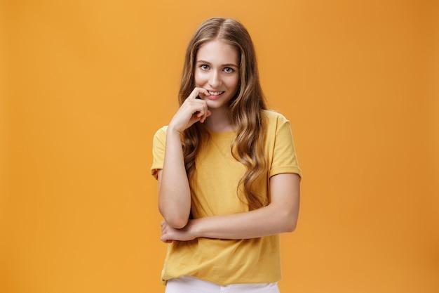 Творческая хитрая молодая женщина с естественными волнистыми длинными волосами в желтой футболке смотрит из-под лба с намерением и похотью в выражении, кусая палец, улыбаясь в камеру над оранжевой стеной.