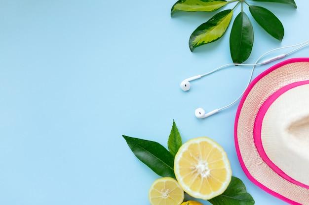 創造的な熱帯の夏の旅行のレイアウト。レモン、イヤポッド、帽子。青い背景。フラットレイ。休暇の概念。過去をコピー