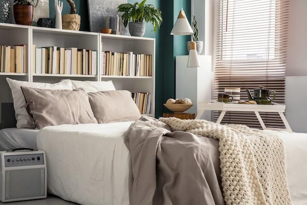 디자이너 장식과 아늑한 흰색 및 베이지색 침구를 갖춘 세련된 침실 인테리어의 작은 공간을 창의적으로 활용
