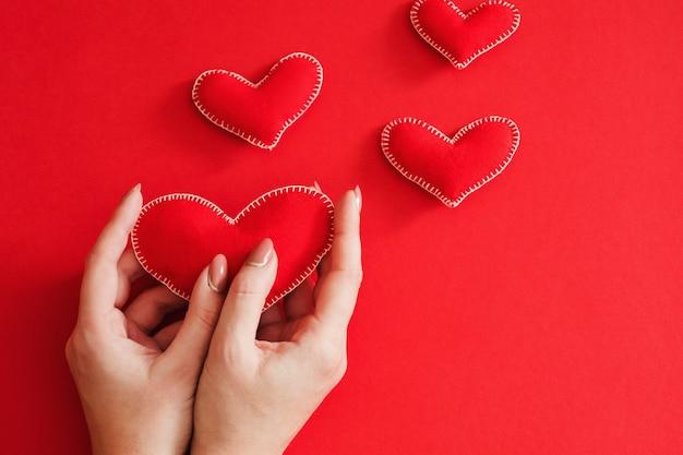 Творческий подарок на день святого валентина. плоская планировка из фетровых сердечек ручной работы на красном