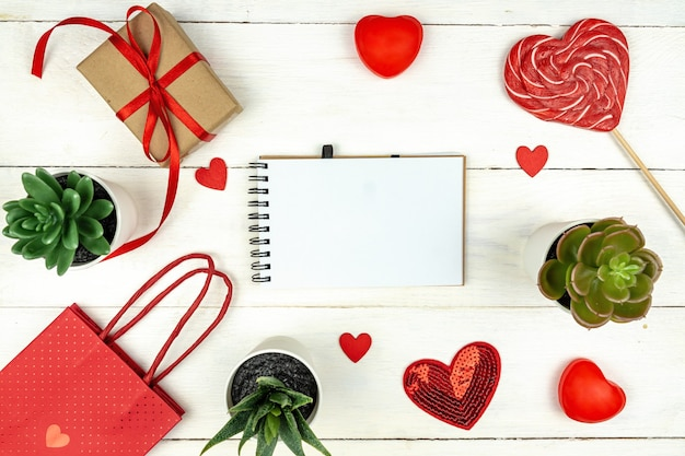 Creative valentine day romantic composition with red hearts, lollipop, gift box and paper bag on white background.