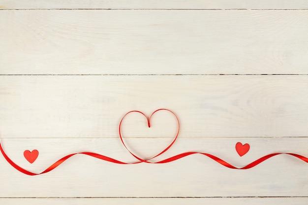 赤いハート、木製の背景にサテンのリボンで創造的なバレンタインデーのロマンチックな構成。ブログやソーシャルメディア用のコピースペースを備えたモックアップ。