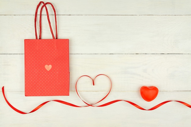 Creative valentine day romantic composition with red hearts, satin ribbon and paper bag on wooden background. mockup with copy space for blogs and social media.