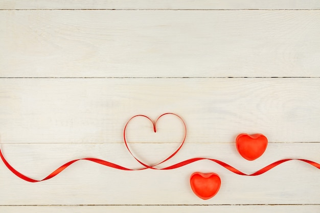 Creative valentine day romantic composition with red hearts, satin ribbon on wooden background. mockup with copy space for blogs and social media.