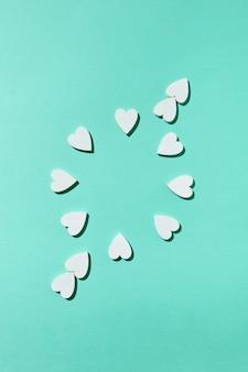Креативная круглая рамка валентинки из гипсовых сердечек ручной работы с диагональной стрелкой на светло-бирюзовой стене с жесткими тенями, копией пространства. плоская планировка.