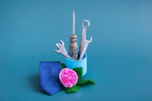 도구가 있는 창의적인 꽃병: 드라이버, 렌치. 컬러 배경에 분홍색 장미, 파란색 넥타이, 도구가 있는 꽃병. 아버지의 날을 위한 미니멀리즘. 클로즈업, 흑백. 정물