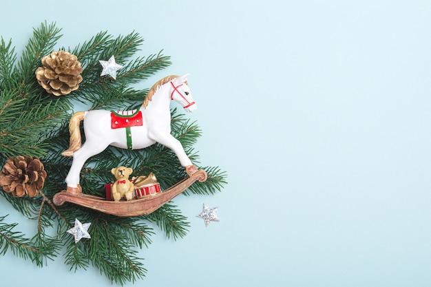 クリエイティブなヴィンテージのミニマルなクリスマスアートの構成。クリスマスのレトロなおもちゃの馬、モミの枝、水色の背景に松ぼっくり。フラットレイ。スペースをコピーします。