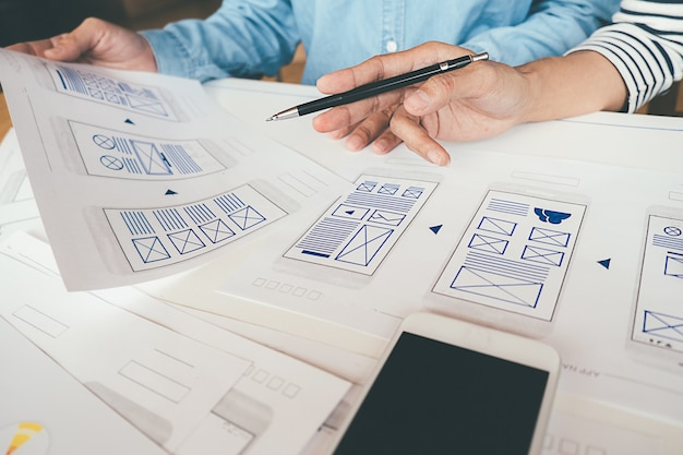 Creative web designer planning application and developing template layout, framework for mobile phone.