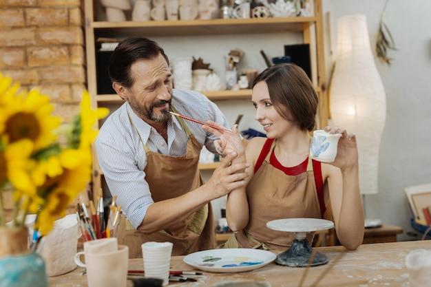 창조적 인 아내. 그의 창조적 인 매력적인 아내의 작업장에 오는 수염 난 검은 머리 잘 생긴 도공