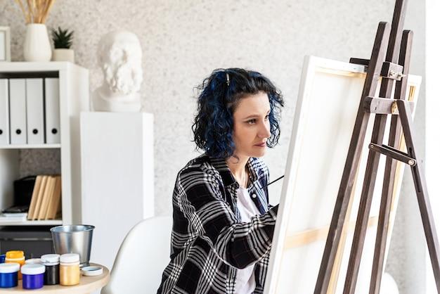 彼女のスタジオで働く絵を描く創造的な女性アーティスト
