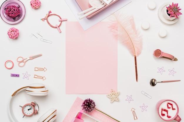 Творческий женский стол вид сверху с розовым чистым листом бумаги