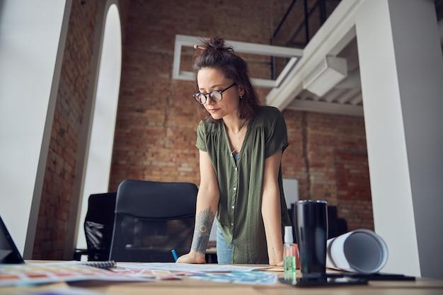 청사진을 보고 있는 지저분한 머리를 가진 평상복을 입은 창의적인 여성 인테리어 디자이너 또는 건축가