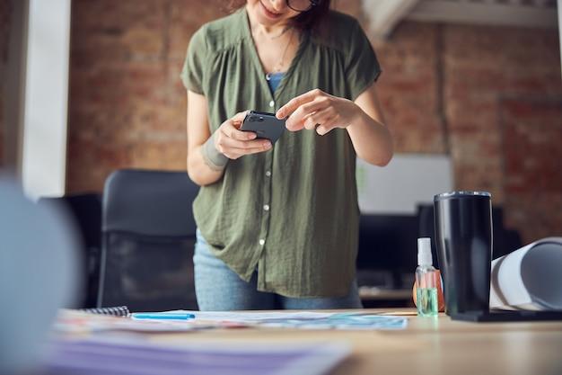 창조적 인 여성 인테리어 디자이너 또는 건축가는 문자 메시지를 보내거나 청사진을 사용하여 사진을 찍습니다.