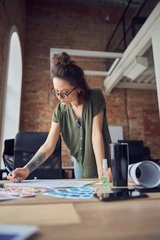작업하는 동안 펜으로 메모를 작성하는 안경을 쓴 창의적인 여성 인테리어 디자이너 또는 건축가