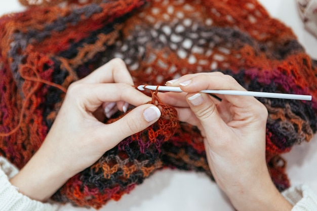 Creative woman knitting a scarf with earth tones of color