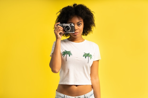 Creative woman-photographer takes photos, isolated on yellow.