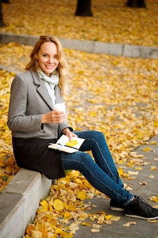 Creative woman with paper notebook and coffee in golden autumn park looking at camera full height