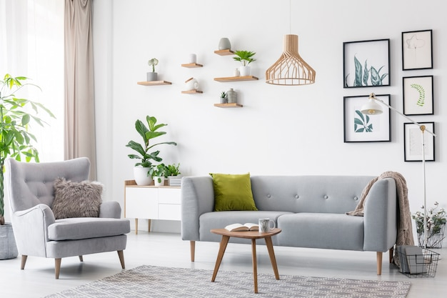 Creative wooden pendant light above a gray sofa and a comfy armchair in a scandinavian living room
