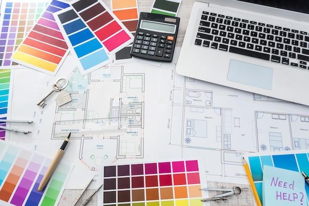 家のスケッチ、電卓、カラーサンプラーを備えたオフィスのラップトップでの創造的な仕事。建築家デザインプロジェクト