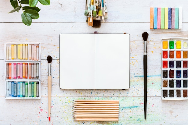 Creative work desk for self-expression, paint brushes, paintbox with watercolors, crayons, pencils and notebook paper on white wooden background, artistic workspace. top view, flat lay, copy space