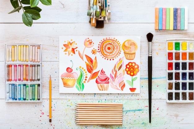 白い木製の背景、フラットレイアウトにペイントブラシを備えた創造的な仕事机