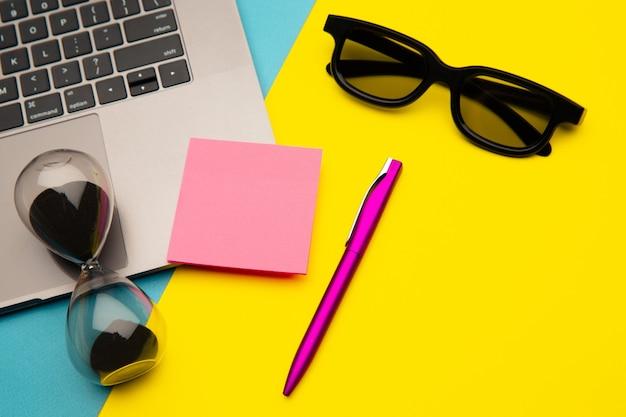 창의적인 작업 공간. 노트북 키보드, 안경, 펜 및 모래 시계가있는 작업 공간 책상의 사진.
