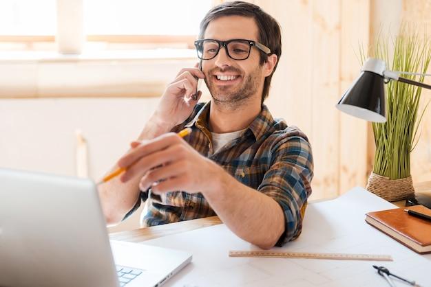 창조적 인 노동자. 쾌활한 젊은 남자가 휴대전화로 통화하고 작업장에 앉아 노트북을 가리키고 있습니다.