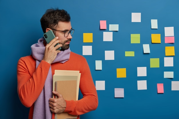 Creative worker with beard calls someone via cellphone, wears eyeglasses, sweater with scarf, looks aside on colorful notes stuck on blue wall