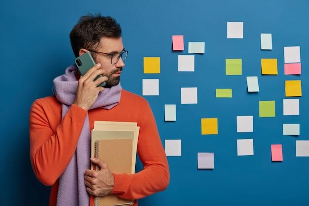 수염을 가진 창조적 인 노동자는 핸드폰으로 누군가에게 전화를 걸고, 안경을 쓰고, 스카프가 달린 스웨터를 입고, 파란색 벽에 붙어있는 화려한 노트를 옆으로 쳐다 봅니다.