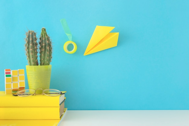 Creative workplace in blue and yellow colors with cactus