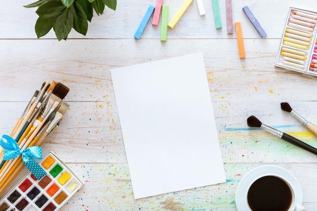 白い木製の背景を描くための創造的な職場。コピースペース、フラットレイアウト