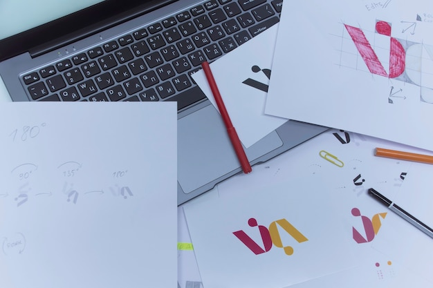 Creative workplace of a graphic designer. development of a logo for the company. drawings and sketches on paper in a art studio office.