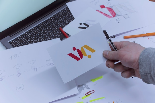 Creative workplace of a graphic designer. a man in the office is developing a logo on the table against the background of printed sketches and a laptop. Premium Photo